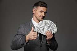 Satisfied lucky chief man 30s in business suit holding fan of cash money dollar currency and showing thumb up isolated over gray background