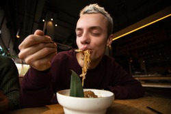 Satisfied man enjoys food in the restaurant. Blong attractive young man with pierced nose puts pasta into his mouth and closes his eyes with pleasure. Tasty food concept.