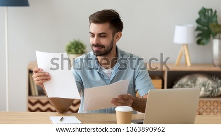 Satisfied man reading paper documents, letters, receiving pleasant news, working with laptop at workplace, sitting on desk, successful businessman, freelancer looking at contract with good offer
