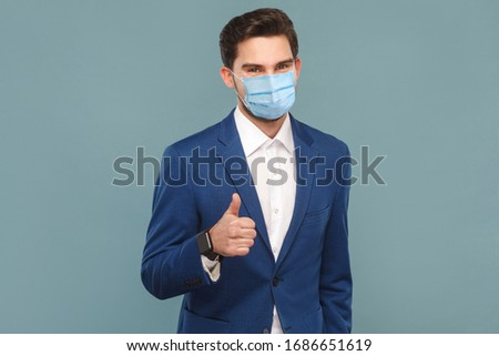 Satisfied man with surgical medical mask showing like sign thumbs up at camera. Business people medicine and health care concept. Indoor, studio shot on light blue background