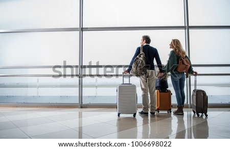 Satisfied man, woman and girl looking out from big window at the airport. They are taking pleasure in airplanes moving along the runway. Copy space in left side