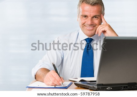 Satisfied mature businessman smiling in his modern office at work