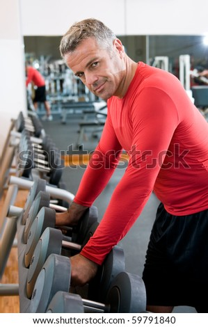 stock photo : Satisfied mature man picks up dumbbells from the rack at gym