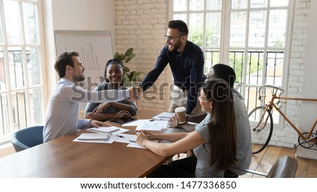 Satisfied middle eastern boss handshake male employee at group meeting thanking for good work, greeting welcoming new worker or client negotiation shake hand of partner at corporate tea
