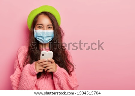 Satisfied mixed race woman has flu, wears protective medical mask not to infect other people, uses cell phone for surfing internet, reads how to cure disease online, dressed in fashionable clothes