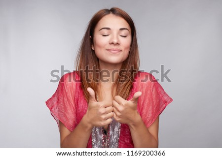 Satisfied mixed raced student showing thumbs up, demonstrating excellent results during exams at university. Close up of young brunette woman closing eyes from pleasure isolated against grey wall.