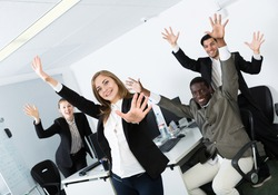 Satisfied multinational business team expressing satisfaction with teamwork at office, enjoying and hands up..
