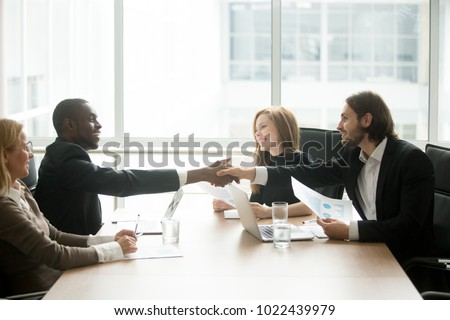 Satisfied multiracial businessmen in suits shaking hands at executive team office meeting, two diverse african and caucasian partners handshaking after multi ethnic negotiations over conference table