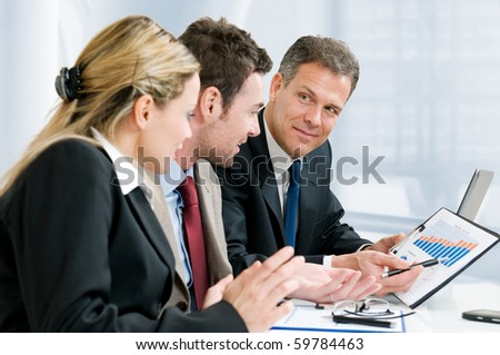 Satisfied senior businessman showing growing chart at his happy colleagues in office