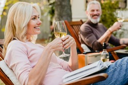 Satisfied senior woman holding a glass of wine talking with her grey-haired husband in the garden