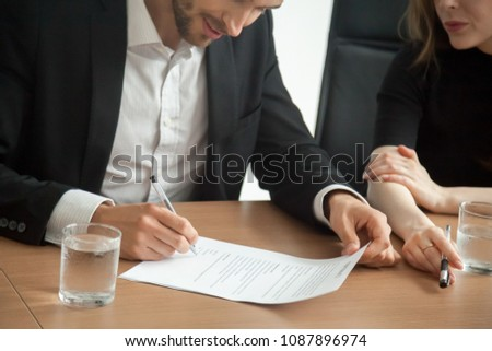 Satisfied smiling businessman in suit signing contract at meeting concept, investor or entrepreneur putting written signature on business document making good partnership deal, taking loan insurance