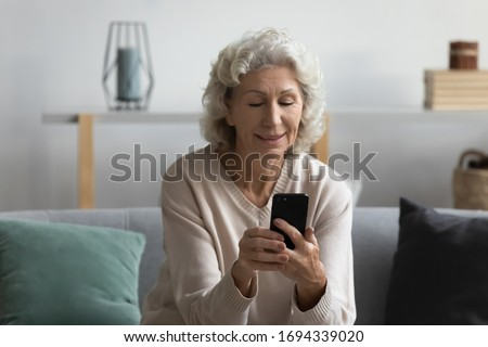 Satisfied smiling positive middle aged woman resting on comfortable couch, using mobile applications, chatting with friends in social networks, reading news in media, shopping online alone at home.
