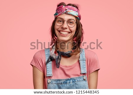 Satisfied smiling woman has broad smile, belongs to hippie subculture, wears transparent glasses, rejoices good news, isolated over pink background. Joyful hippy in headband models alone indoor