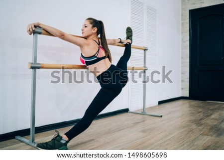 Satisfied successful shapely flexible brunette woman in sportswear and sneakers stretching on barre doing splits in modern studio and looking away