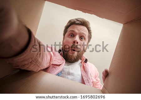 Satisfied, surprised man holds out his hand, trying to get a gift or parcel from an unpacked box. Unboxing inside view.