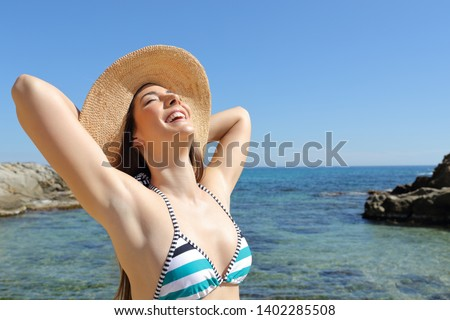 Satisfied tourist enjoying summer vacation and sun on the beach
