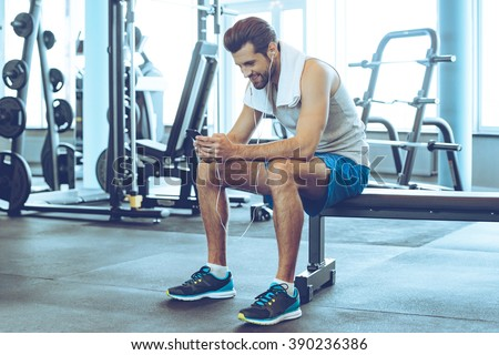 Satisfied with his work out. Handsome young men in headphones using his smart phone with smile while sitting at gym #390236386