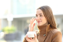 Satisfied woman applying mousturizer cream on her face in winter in the street