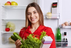 Satisfied woman holds fresh vegetables and milk, going to put them in refridgerator, has broad smile and happy expression, being vegeterian, eats only healthy food. People and nutrition concept