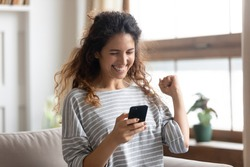 Satisfied woman reading good news in email or social network message close up, excited girl looking at phone screen, showing yes gesture with hands, celebrating success, online lottery win
