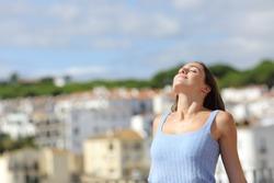 Satisfied woman relaxing breathing fresh air in a rural town