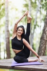 Satisfied young brunette woman in black sportswear practices yoga, doing Surya Yantrasana exercise, sitting in a compass pose on a wooden bridge in the park