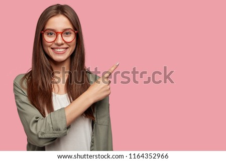 Satisfied young female with positive expression, attracts your attention at copy space aside, demonstrates some items in shop, dressed in casual shirt, has dark straight hair, isolated over pink wall #1164352966