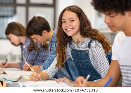 Satisfied young woman looking at camera. Team of multiethnic students preparing for university exam. Portrait of girl with freckles sitting in a row with her classmates during high school exam.