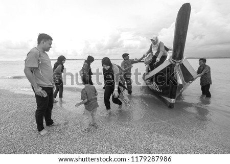 Satun, Thailand - 1 September, 2018 : Tourists from Malaysia on wooden boat service at Dragon Spine beach in Satun. Satun is a southern province of Thailand.  #1179287986