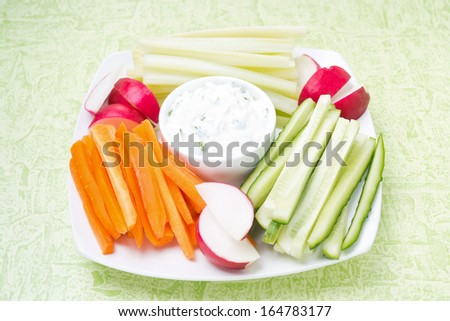 sauce with feta cheese and assorted vegetables on a plate on green background, close-up - stock photo