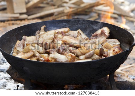 saucepan of bacon frying in fire