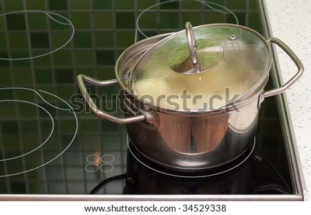 Saucepan with boiling food stand on ceramic lash