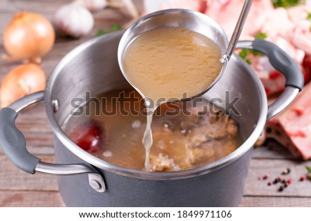 Photo of  Saucepan with bouillon with a ladle on the table. Bone broth
