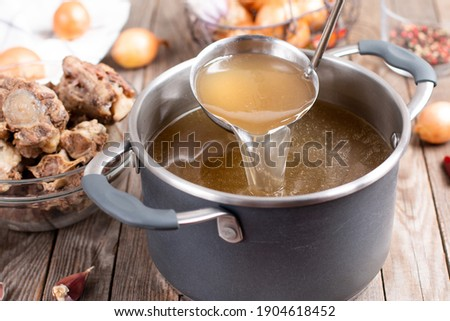 Saucepan with bouillon with a ladle on the table. Bone broth Сток-фото ©