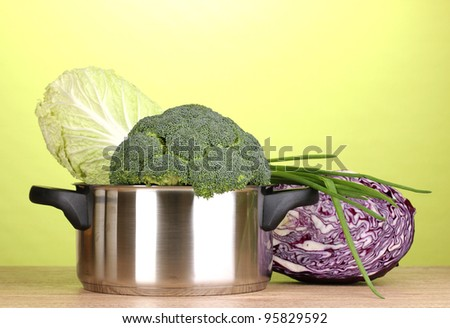 Saucepan with broccoli and cabbages on wooden table on green background