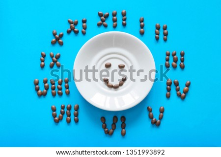 Saucer with a smile and clock made of cocoa beans on the blue background.