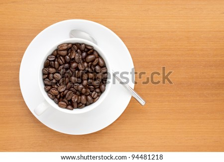 Saucer with cup of coffee beans with spoon - stock photo