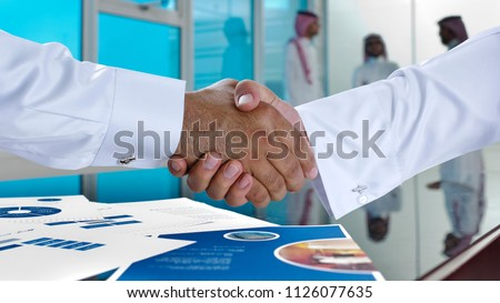 Saudi Arab businessmen shaking hands, and making agreement or a deal in a meeting room