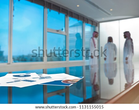 Saudi Arab businessmen talking in a meeting room, focus on ducuments on the table