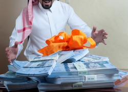 Saudi Arab man surprized with stacks of money on the side table at home