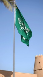 Saudi Arabia flag in front of an old building of the older part of Riyadh