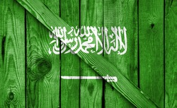 Saudi Arabia flag is depicted on a wooden background close-up