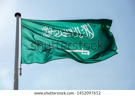 Saudi Arabia flag, National symbol waving against clear blue sky, sunny day