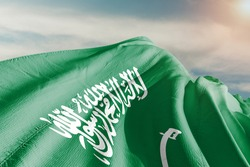 Saudi Arabia national flag cloth fabric waving on beautiful sky.