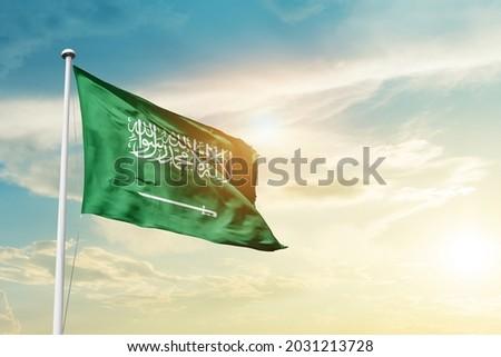 Saudi Arabia national flag waving in beautiful clouds.