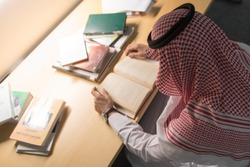 Saudi Arabian Man Reading a Book in The Library