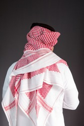 Saudi Arabian man wears traditional Saudi Clothes (Shmag). Photograph portrait from behind.
