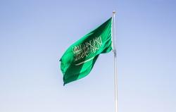 Saudi Arabian national flag weaving on wind with blue sky background in Riyadh city, near Masmak fort