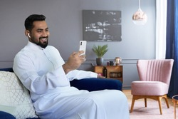 Saudi man video calling at home sitting at sofa in living room