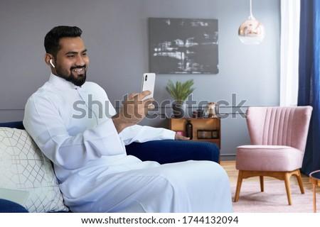 Saudi man video calling at home sitting at sofa in living room